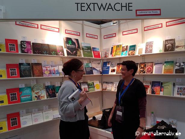 Zwei Frauen, die sich an einem Stand der Leipziger Buchmesse 2019 unterhalten.
