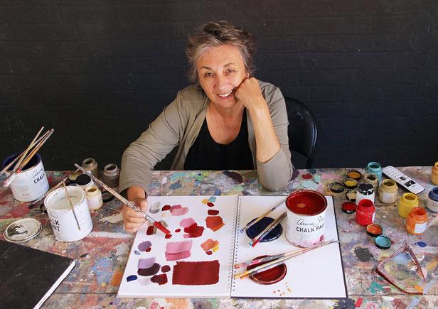 Auf dem Foto sieht man eine Frau an einem Tisch sitzen. Sie hat einen Pinsel in der Hand und experimentiert mit der Kreidefarbe. Es ist Annie Sloan.