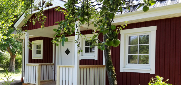 überdachter Eingangsbereich von rotem Holzhaus von Berg Schwedenhaus