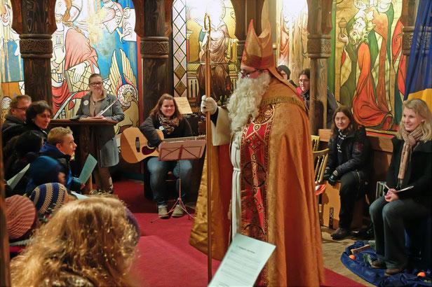 Nikolaus steht in der Kirche des Europaparks. Im Hintergrund sieht man die bunten Kirchenfenster. Um ihn herum sitzen Kinder und Jugendliche mit Musikinstrumenten und Liederzetteln in den Händen.