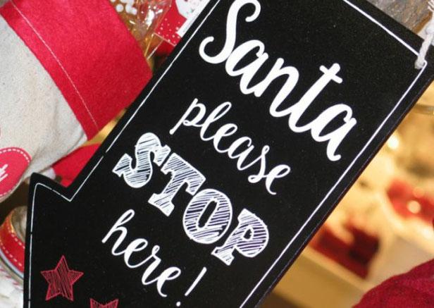 """Auf einem schwarzen Holzschild steht in weißen Lettern geschrieben: """"Santa, bitte stopp hier"""".  Hinter dem Schild sind weiß-rote Dekogegenstände zu sehen."""