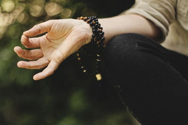 Hand einer meditierenden Frau, mit schwarzen Armbändern