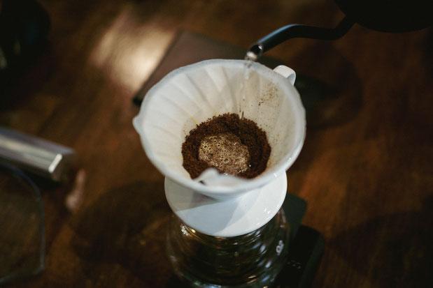 Wasser wird langsam auf den Kaffee gegossen, um diesen zu benetzen.