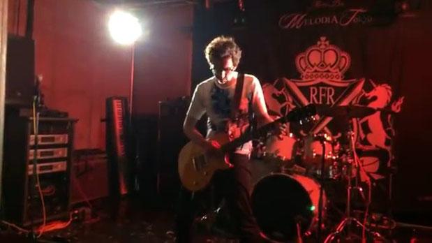 マウロがメロディアトーキョーのステージでギターソロを演奏している場面