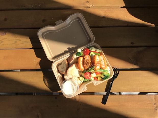 日替わりランチサラダの写真。パプリカ、ブロッコリー、アボカドなどたくさんの種類のサラダの上にエビカツが乗っている。パンも一緒に。