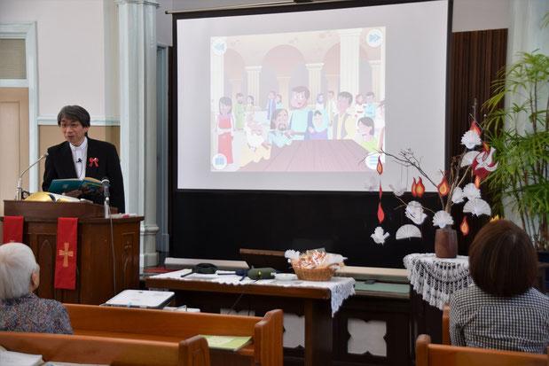講壇の上に設置されたスクリーン。ペンテコステの出来事、新世代の紙芝居で紹介中。
