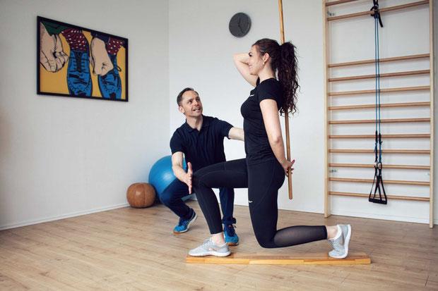 eine Sportlerin macht eine einbeinige Kniebeuge auf einem Brett