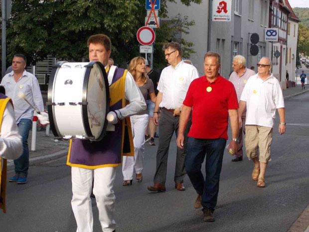 Der Dieter-Bessler-Spielmannszug, der IG Vorstand, Bürgermeister Rafael Reißer und Bezirksverwalter Achim Pfeffer marschieren zum Rathausplatz, um die Kerb zu eröffnen.