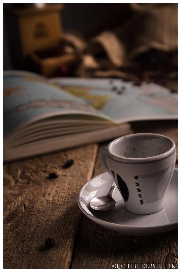 Tasse Espresso mit Atlas und Kaffeemühle im Hintergrund