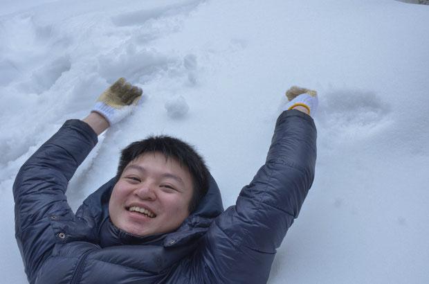 雪の上に寝転ぶ、台湾からの留学生・蔡(サイ)さん。