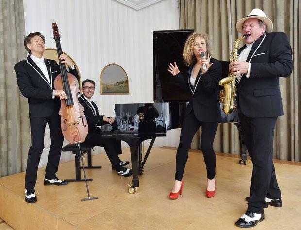 Band mit Flügel, Bass, Saxophon und Sängerin