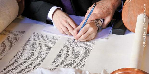 Die Hand eines Sofers hilft beim Schreiben der letzten Buchstaben.