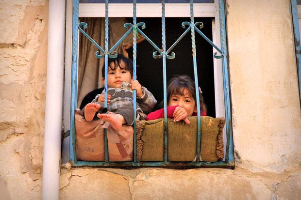 Kids sitting behind the window in the Old city of Nablus... © Sabrina Iovino | JustOneWayTicket.com