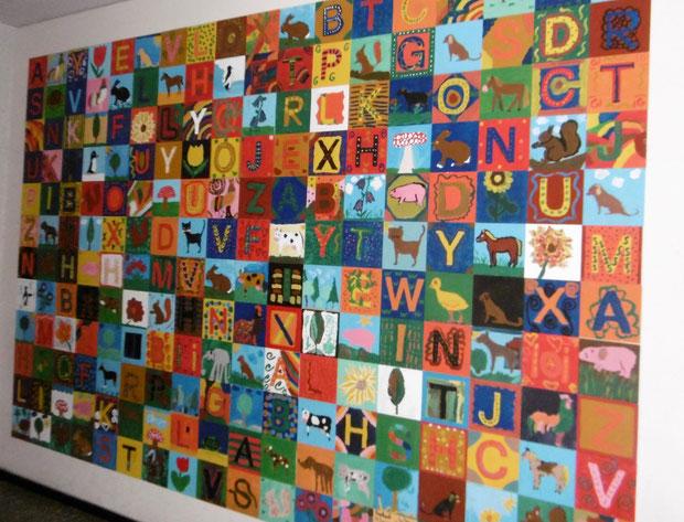 Bild aus dem Schulgebäude das farbige Kacheln mit Buchstaben zeigt