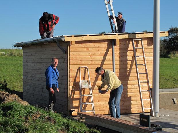 13.10.2011 - Das Dach wird montiert. Auf dem Dach Manfred Habenicht und Dieter Kirchner. Davor Peter Matzen (v.l.) und Horst Hansen.