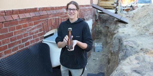 Julia Rohlf freut sich über den Fund auf der Baustelle ihrer neuen Brauerei im Gewerbegebiet Nordwest: Eine annähernd 100 Jahre alte Bierflasche. Quelle:Johanna Stein