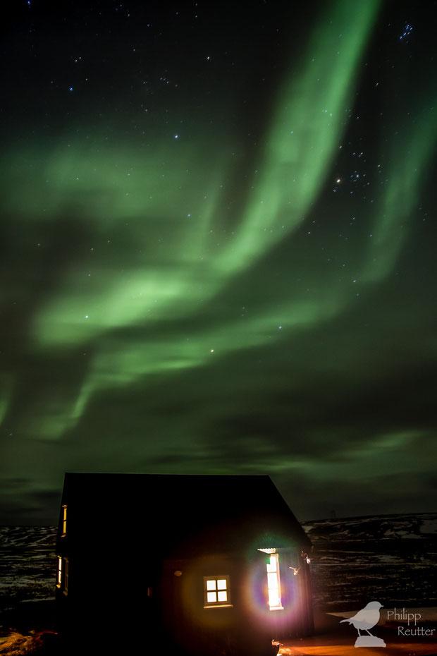 Polarlicht und Plejaden über der gemütlichen Hütte