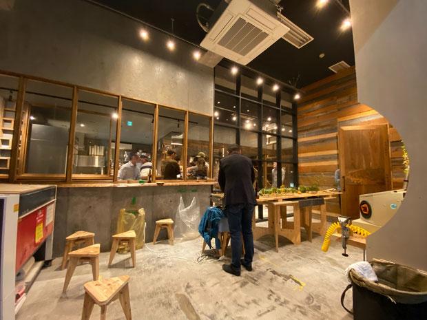レーザーカッターもある広い工房空間(ガラス越しにカフェスペースが広がります)