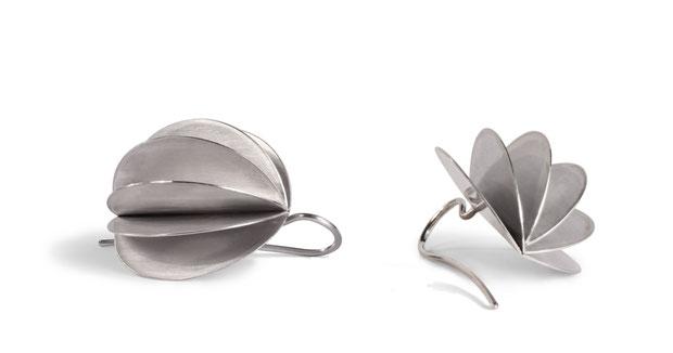 Die aufregenden Ohrhänger LAMPION aus Silber erzeugen ein faszinierendes Farbenspiel aus Silbertönen. Das Licht bricht und reflektiert sich auf den Flächen des aufgefächerten Lampions und verleiht dem Ohrhänger Leben