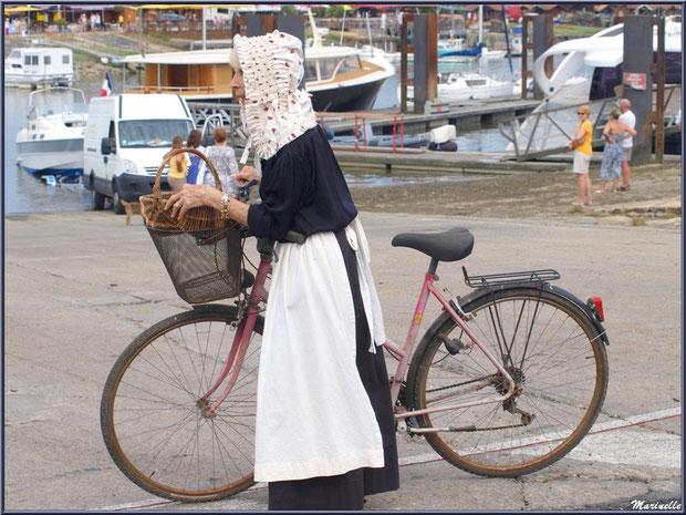 Femme avec son vélo, en tenue locale, coiffée de sa benaise, attendant le retour des pêcheurs de sardine - Fête du Retour de la Pêche à la Sardine 2014 à Gujan-Mestras, Bassin d'Arcachon (33)