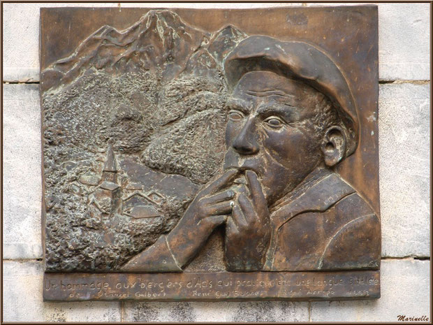 Plaque commémorative, représentant un siffleur, sur un des piliers du porche d'entrée de l'église Saint Laurent, village d'Aas, Vallée d'Ossau (64)
