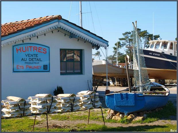 Cabane 34-35 avec sa déco de tuiles chaulées et son canot fleuri à l'entrée du port ostréicole d'Andernos-les-Bains et, en fond, bateaux en cale sèche - Bassin d'Arcachon