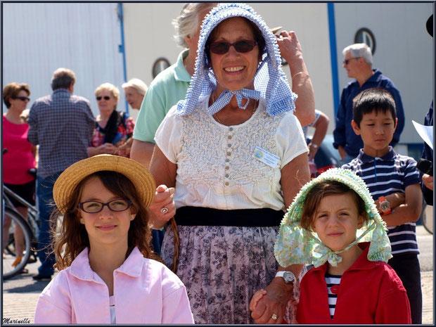 Femme et fillettes, en tenue locale, attendant le retour des pêcheurs de sardine - Fête du Retour de la Pêche à la Sardine 2014 à Gujan-Mestras, Bassin d'Arcachon (33)