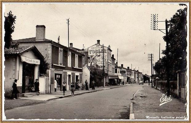 """Gujan-Mestras autrefois : vers 1930, Cours de la République (dans l'autre sens) avec le magasin """"De Tout un Peu"""" et l'hôtel """"Les Pyrénées"""" (avec pub Tobler au mur) et, à droite, la propriété Dr Bézian, Bassin d'Arcachon (carte postale, collection privée)"""