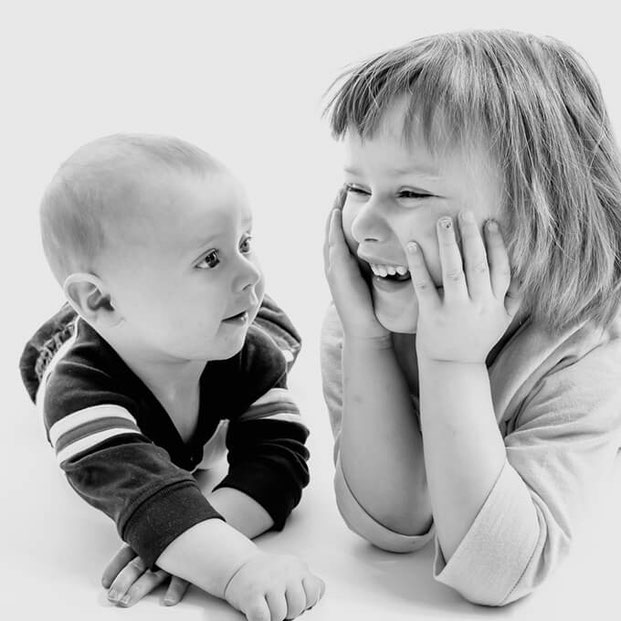 Black and white photo of sister and brother lying on their stomaches smiling at each other. Brother is a baby. Sister is a young child. Background is white.