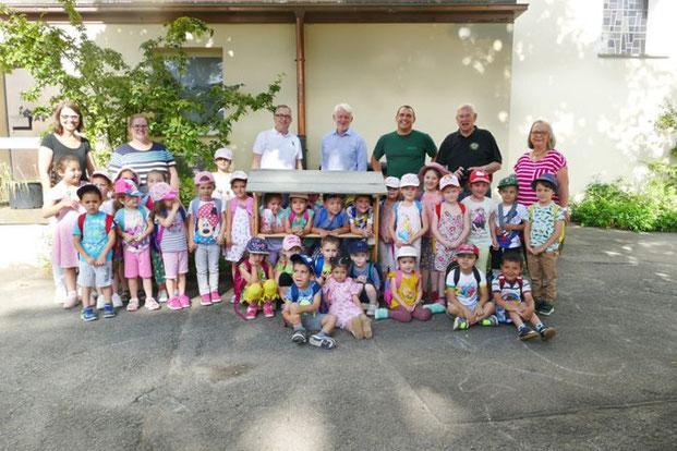 Die Kinder und Erzieherinnen des Kindergartens Wilhelmspflege freuen sich über das neue Insektenhotel, das ihnen die Vertreter der Lions Freizeitwerkstatt und der stellvertretenden Forstamtsleiter Roland Brauner vorbeigebracht haben. Foto: Riesterer