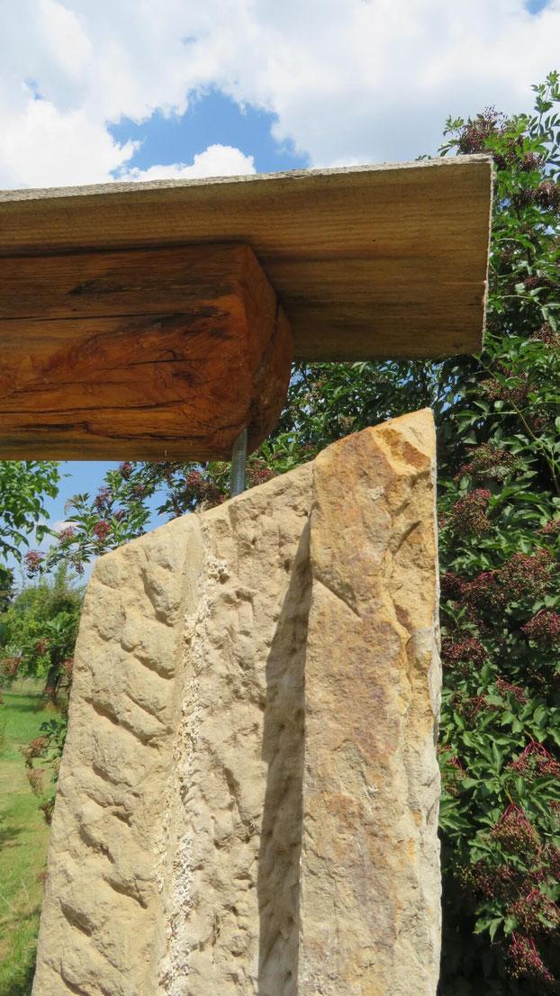 Für die rechte Seite des Tores wurde ein alter, behauener Sandstein-Pfeiler verwendet.  Ein kurzes, rundes Eisenstück überbrückt die fehlende Höhe zum Dach.