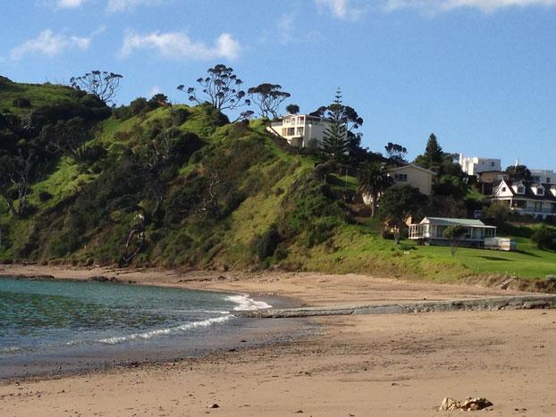 Meer und Sandstand, grüner Hügel mit Häusern