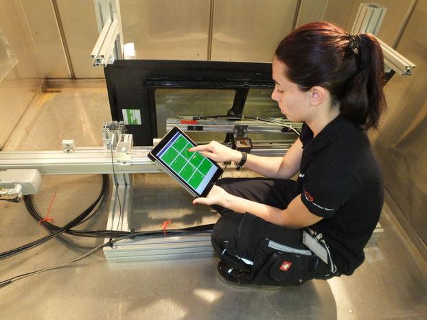 Eine Mitarbeiterin überprüft und steuert mit einem Tablet den Versuchsaufbau