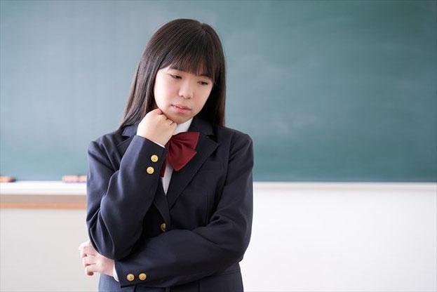 教室で悩んでいる女子中学生