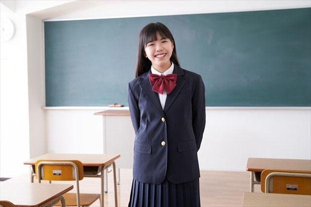 学校の教室で微笑む中学生