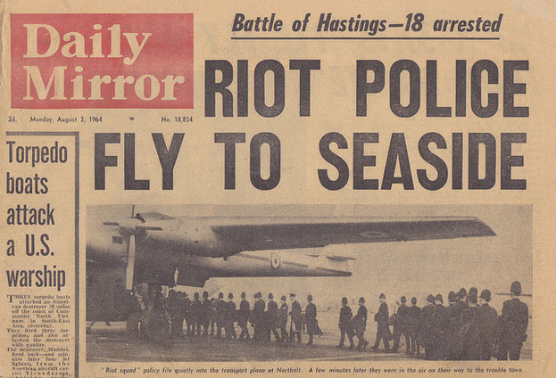 British culture: photo of a copy of the Daily Newspaper showing police boarding a military  plane during mod and rocker disturbances.