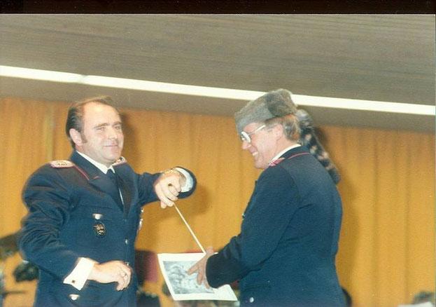 1985: Der 1.Vorsitzende Manfred Schmidt überreicht Dirigent Johannes Kreipe eine Trappermütze zu den Winnetou-Melodien