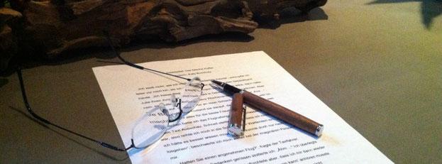 Auf dem Tisch der Delmenhorster Schriftstellerin Katy Buchholz befinden sich ein beschriebenes Blatt Papier, ein Stift mit Holzgriff und eine Brille.