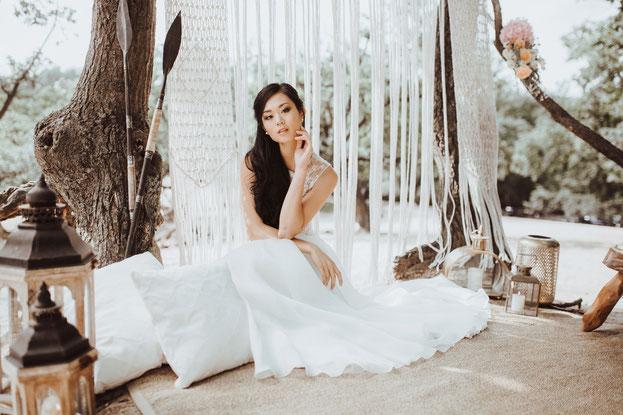 Schöne Braut mit Hochzeitsmakeup im Bohostyle mit langen schwarzen Haaren und weißem Spitzen Hochzeitskleid
