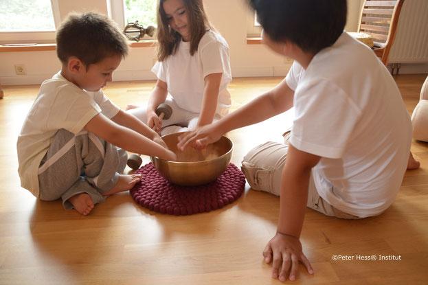 Drei Kinder spielen mit einer Klangschale und entdecken den Klang