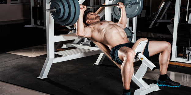 muskulöser Athlet stemmt schwere Gewichte in einem Fitnessstudio