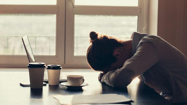 Femme brune épuisée qui dort devant son ordinateur. Il y a trois tasses de café sur la table.