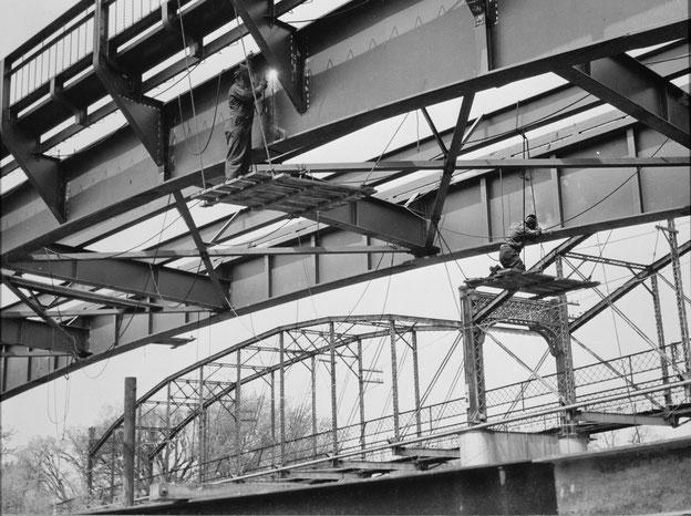 Ansicht, die Schweißer bei der Arbeit an den Nord- und Südträgern zeigt, mit der alten Brücke im Hintergrund, Blick nach Nordwesten , um den 10. Mai 1949