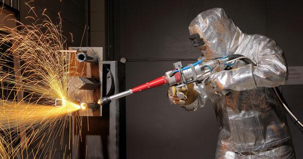 Laserschneiden im Schutzanzug mit einem von Hand gehaltenen Laserstrahlkopf