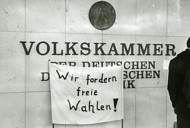 Transparent vor Volkskammergebäude mit Aufschrift Wir fordern freie Wahlen