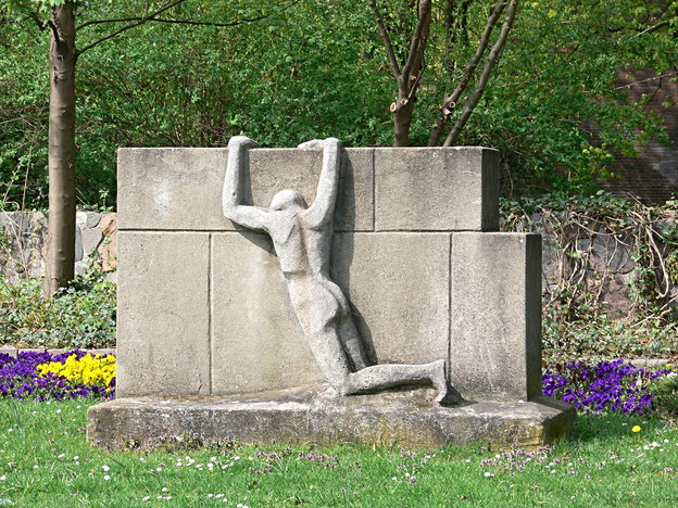 Mann zieht sich an Mauer hoch. Denkmal zum Leid an der Mauer