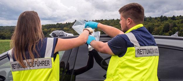 Rettungshundeführer nehmen bei einer Einsatzübung den Geruch der vermissten Person mithilfe von Mullbinden ab. Dabei tragen sie Handschuhe, um den originalen Geruchsträger nicht zu kontaminieren.