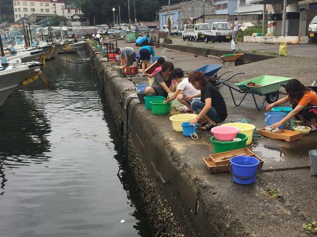 お供えに使ったものを海で洗う。