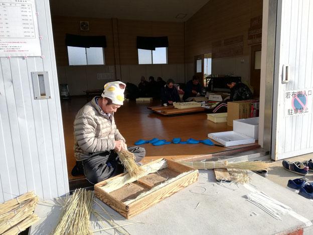 木箱に敷く藁を束ねているおじさん