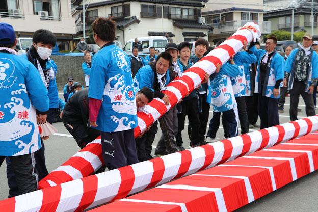 棟持柱を持ち上げる青年たち